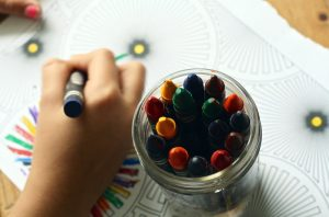 child's hand while doing color