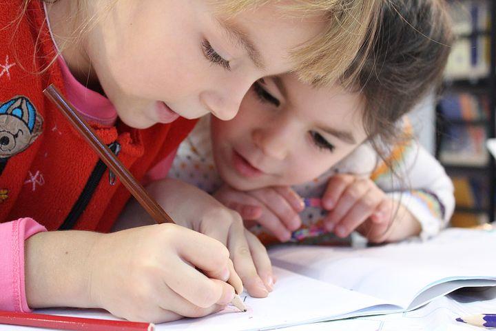 Two little girls writing