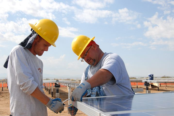 Two people installing 3 phase solar inverter