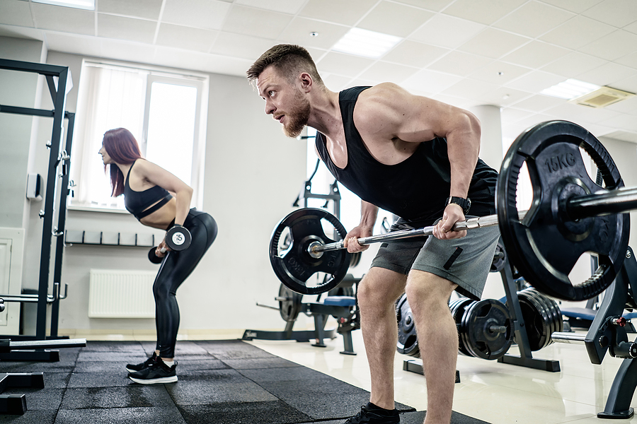 A man and a woman while using adjustable dumbbells and barbell set