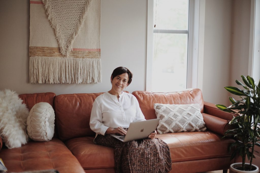 Woman sitting in a leather sofa while using her laptop