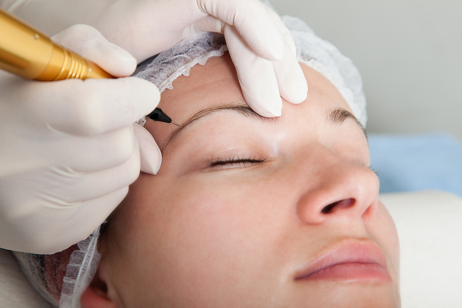 Cosmetologist making permanent makeup on eye brows