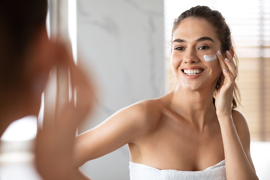 Woman applying Divine Woman product on her face